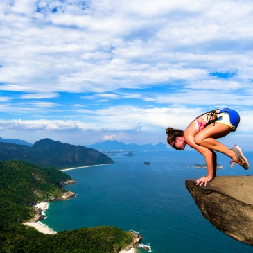 Crow pose on cliff in Brazil