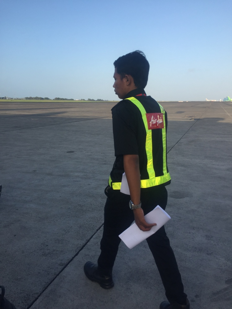 Air Asia staff escort onto plane at Denpasar International Airport in Bali, Indonesia