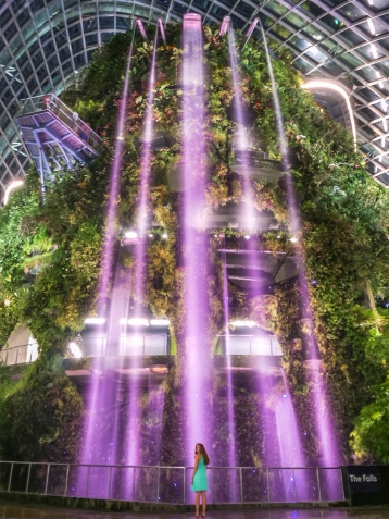 Travel girl at Cloud Forest indoor waterfall at night