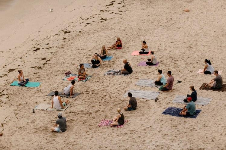 Beach yoga class with out of town wedding guests in Spain. Photos by Jonathan Gipaya
