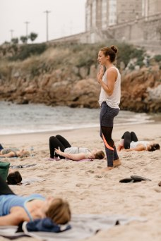 Instructing bridge pose during beach yoga
