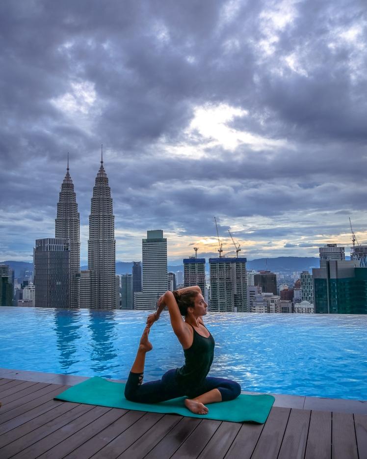 Rooftop pool sunrise in Kuala Lumpur with yoga pose