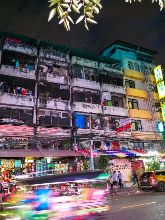 Tuk-tuk whizzes by a street at night in Bangkok