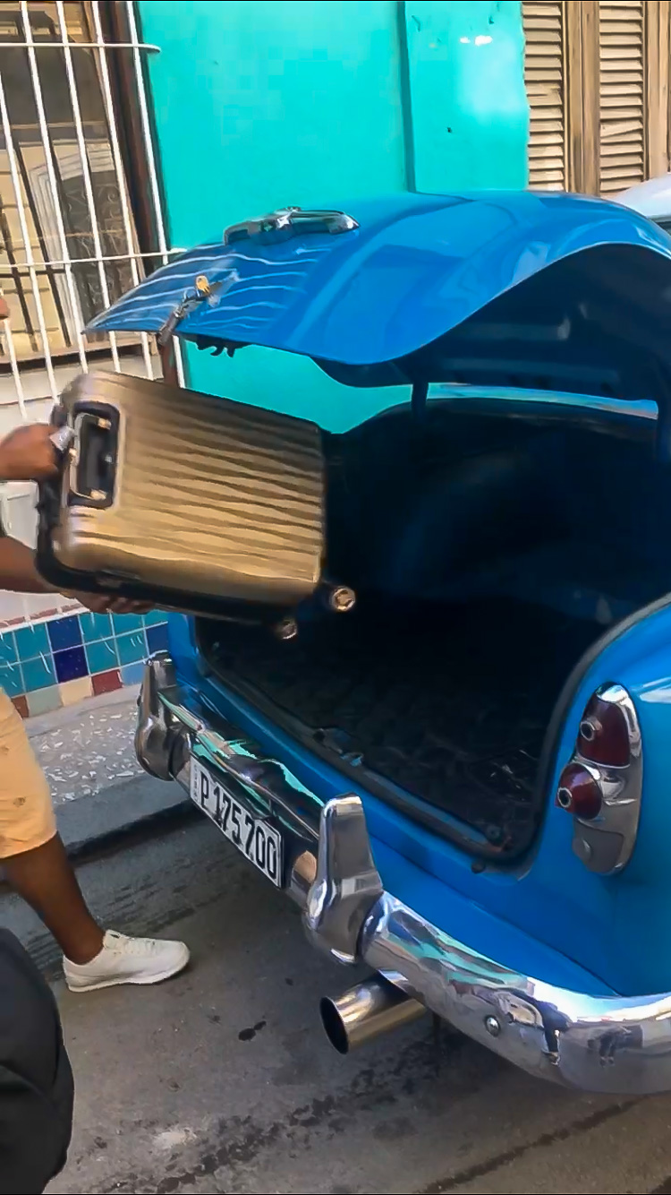Carry-on bag in old cab car trunk in Havana